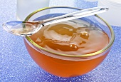 Gelled chicken stock in a glass bowl with plastic spoon