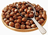 Hazelnuts in a terracotta dish with scoop