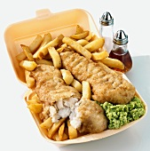 Fish and chips with mushy peas in a polystyrene container