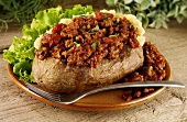 A baked potato with bolognese sauce