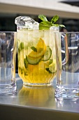 Orange and mint punch in a jug with glasses