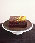 A square chocolate cake with gold