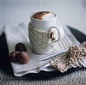 A mug of hot chocolate with chocolates