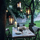 Laid table out of doors at twilight with lanterns
