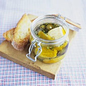 Pickled goat cheese with lemon and olives