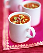 Tomato soup with avocado and diced onion in three mugs