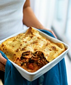 Woman holding dish of seafood lasagne