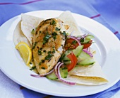 Chicken breast with cucumber-tomato salad on a tortilla