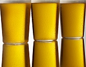 Three glasses of cold lager in a row