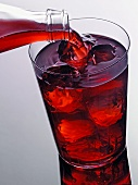 Pouring pomegranate juice out of bottle into glass of ice cubes