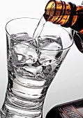 Pouring Cointreau out of bottle into glass with ice cubes