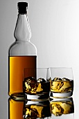 Two glasses of whisky with ice cubes in front of bottle