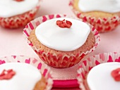 Cupcakes with white icing and red sugar flower