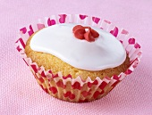 Cupcake with white icing and red sugar flower