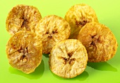 Banana chips on green background