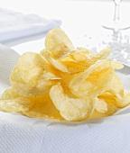 A heap of potato crisps, salt in background