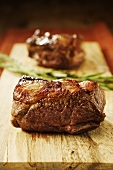 Fried lamb steaks on chopping board
