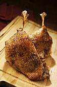 Crispy roast duck legs on chopping board