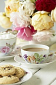Cup of tea, sugar cubes, cookies and roses