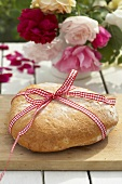 Rustic white bread with checked ribbon on garden table