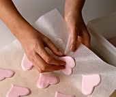 Heart-shaped biscuits being removed from baking paper