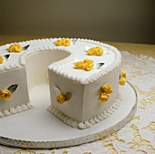 A white cake with yellow sugar roses