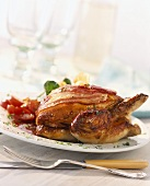 Roasted partridge wrapped in bacon with a redcurrant sauce