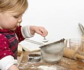Girl sieving icing sugar