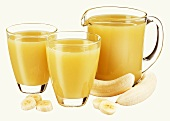 Banana juice in jug and two glasses and fresh banana
