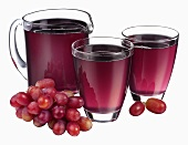 Grape juice in jug and two glasses and fresh grapes