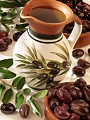A jug of olive oil, olives and olive branches