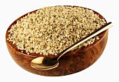 Hemp seeds in a wooden bowl with spoon