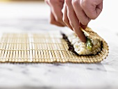 Making maki sushi (rolling up with a bamboo mat)