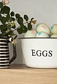 Fresh eggs in a bowl, greenery in jug