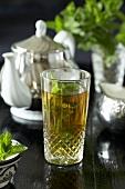Minztee in einem Glas mit Teekanne