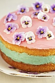 Sponge cake with pink icing and pansies