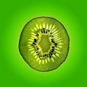 Slice of kiwi fruit against green background
