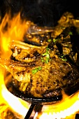 Marinated lamb chops in cast-iron frying pan over a flame