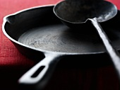 Cast-iron frying pan and soup ladle