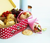 Lunch box with wraps, cookies, grapes and cherry tomatoes