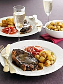 Beefsteak with butter sauce, fried potatoes and tomato salad