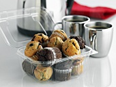 Assorted mini-muffins in plastic container to take away, coffee