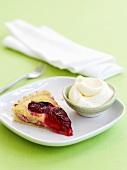 Piece of plum tart with cream
