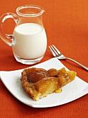 Piece of apple tart and jug of cream