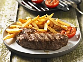 Grilled steak with chips and grilled tomato