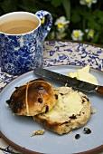 Buttered hot cross bun with tea