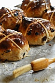 Hot cross buns on a baking tray with pastry brush