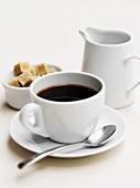 A cup of black coffee, sugar cubes and milk jug