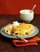 Bread and butter pudding with whipped cream (England)