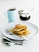 Pancakes with lemon zest and maple syrup, cup of coffee